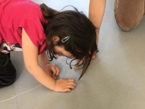 une enfant suit l'index d'un adulte sur le sol